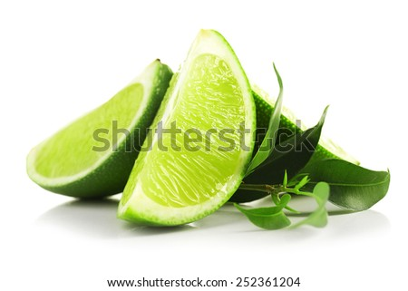 Juicy slices of lime with green leaves isolated on white - stock photo
