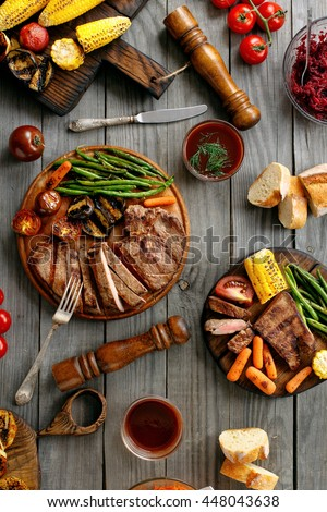 Juicy steak cooked on a grill with grilled vegetables on rustic wooden table, top view. Outdoors food concept