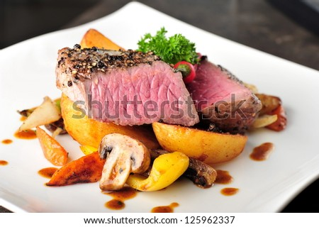 Juicy steak with baked potatoes and mushrooms, Dry aged prime grade beef rib eye steak cooked medium rare. Steak cut fries, pepper, mushrooms and parsley on a plate