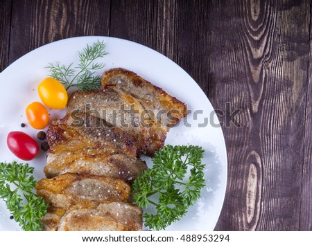 Juicy steak with spices and vegetables . Juicy portions of grilled fillet steak served with tomatoes on an old wood table.