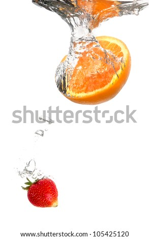 Juicy strawberry and orange under water. Healthy and tasty foods - stock photo