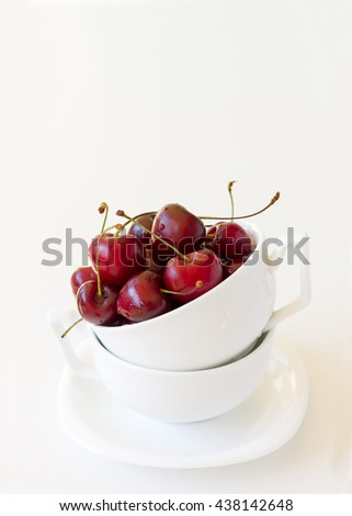 Juicy tasty red sweet cherries in mug on white background. Selective focus and spase for text. - stock photo