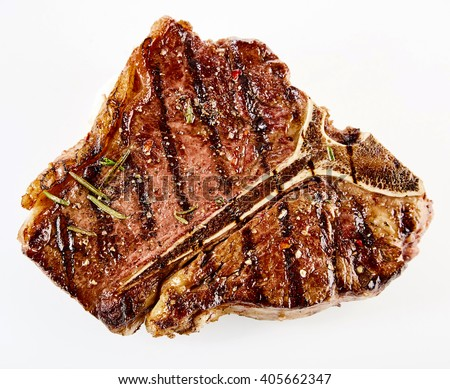 Juicy thick grilled T-bone beef steak seasoned with rosemary fresh of the summer BBQ viewed from above in a close up view over white