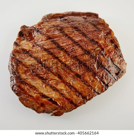 Juicy thick medallion of lean flank beef steak marinated and grilled over a summer BBQ viewed close up from above over white - stock photo