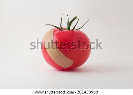 Juicy tomato with one bandage - stock photo