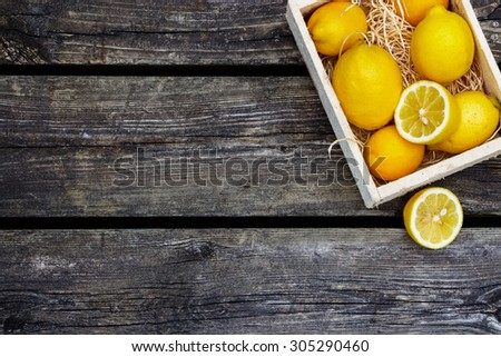 Juicy whole lemons and freshly cut half on rustic wooden background with space for text. Top view. - stock photo
