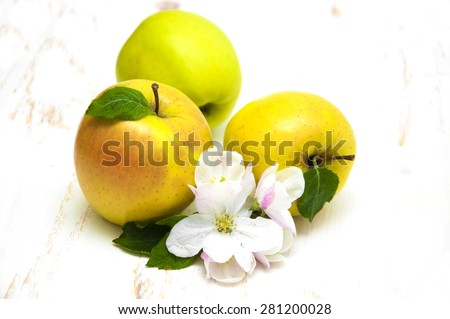 Juicy yellow apple with blossom on a white wooden background - stock photo