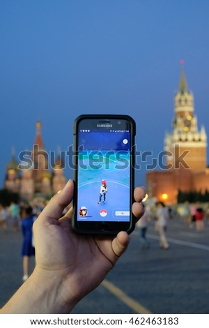 JUL 31, 2016 MOSCOW: Male hand holding a Samsung Galaxy smartphone with a running Pokemon Go application on the background of Kremlin wall and the Saint Basil's Cathedral. Focus on smart phone!!