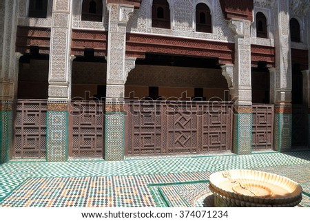 JULY 09, 2015: Ablution fountain and Berber decorations on the walls of Bou Inania Madrasa in Meknes, Morocco