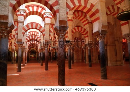 July 12, 2015: Dark interior under the Moorish arches and columns of the Cathedral (Mosque / Mezquita) in Cordoba, Andalusia, Spain