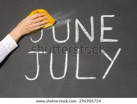 July is coming concept - inscription June and July on a school blackboard, with the words June being erased by the teacher. - stock photo