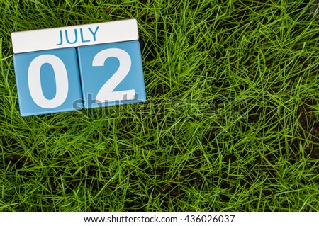 July 2nd. Image of july 2 wooden color calendar on green lawn grass background. Summer day