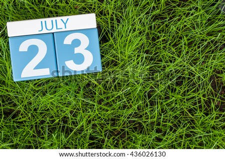 July 23rd. Image of july 23 wooden color calendar on greengrass lawn background. Summer day, empty space for text