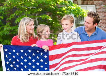 July 4th: American Family Behind US Flag - stock photo