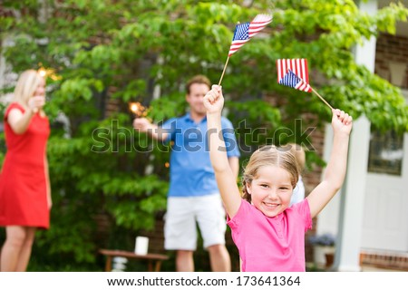 July 4th: Excited Little Girl Holding Flags in the Air - stock photo