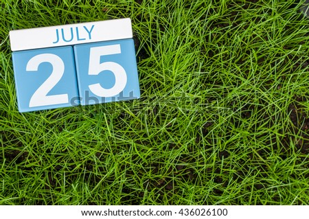 July 25th. Image of july 25 wooden color calendar on greengrass lawn background. Summer day, empty space for text