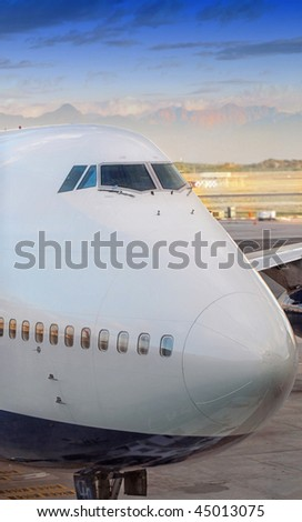 jumbo jet at the airport - sunset and blue sky - stock photo