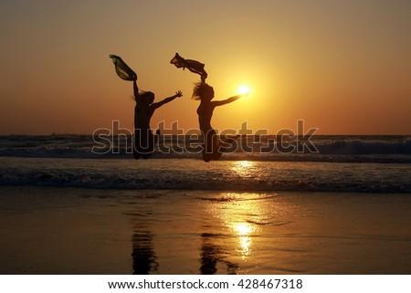 jump at sunset, sunset at sea, girls, fun, funny, wind, ocean - stock photo