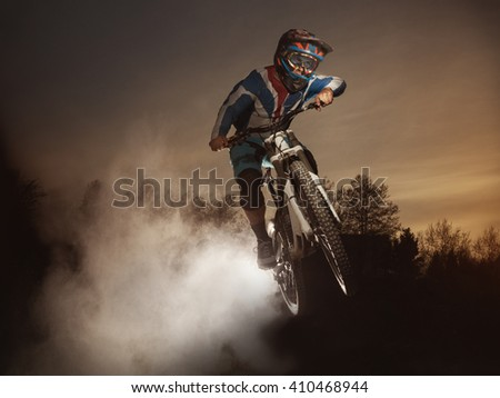 Jump on a mountain bike. Biker making a stunt and jumps in the air. Cool athlete cyclist on a bike flying dust. Downhill biking. MTB - stock photo