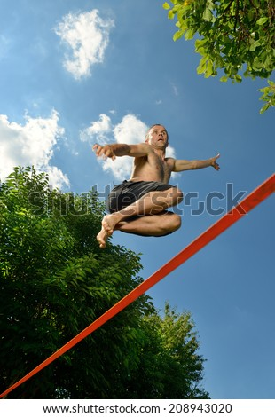 jump to a tightrope walker on a wire - stock photo