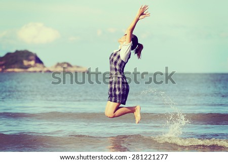 Jump to the freedom, Asian woman jumping on the beach, retro and vintage tone