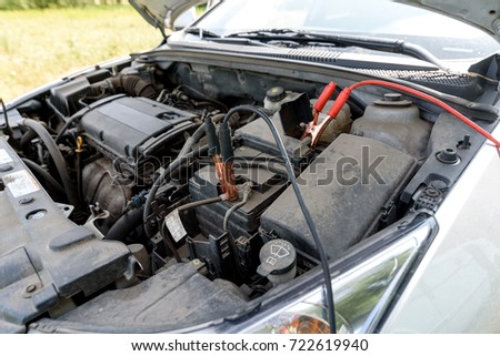 Jumper cables charging battery on car. Red and black car battery booster cables. Charging car battery with electricity trough jumper cables with copper clamps; copy space. Recharging battery on road