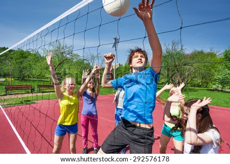 Jumping boy for ball plays volleyball with teens - stock photo