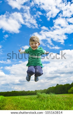 Jumping boy outside. A happy boy jumps on the meadow under blue sky. - stock photo
