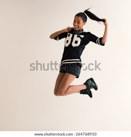 Jumping brazilian girl full body portrait with headphones. Filtered image. - stock photo
