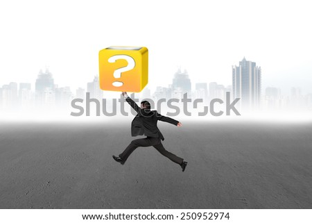 Jumping businessman hitting 3d question mark box with cityscape concrete floor background - stock photo
