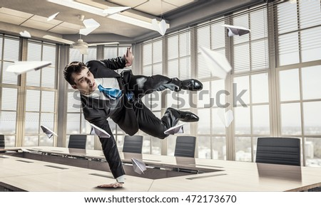 Jumping businessman in office . Mixed media