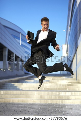 Jumping businessman over urban background