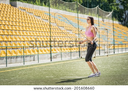 Jumping cheerleader. Young and charming woman in sunglasses and sportswear standing on the football field and jumps on the rope side view - stock photo
