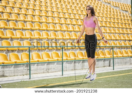 Jumping cheerleader. Young and charming woman in sunglasses and sportswear standing on the football field and jumps on a skipping rope on the background side view of the stands - stock photo