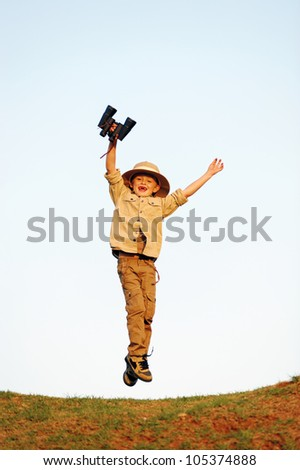 Jumping child explorer with binoculars and safari hat playing adventure games outdoors - stock photo
