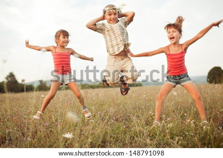 jumping children on a beautiful sunlit meadow in autumn - stock photo
