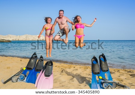 Jumping family on tropical beach - stock photo