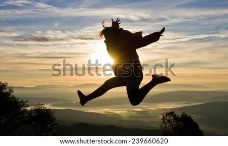 jumping girl against light - stock photo