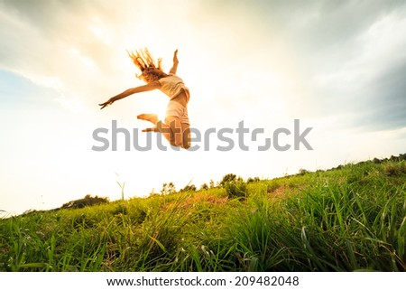 Jumping girl  at field in summer. outdoor shot - stock photo