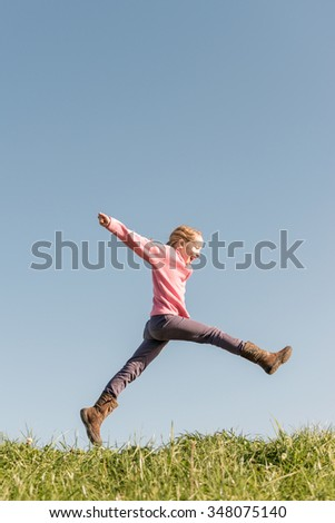 Jumping girl in front of blue sky - stock photo