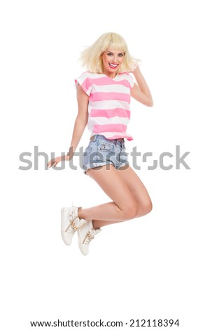 Jumping girl. Smiling blond young woman jumping. Full length studio shot isolated on white. - stock photo