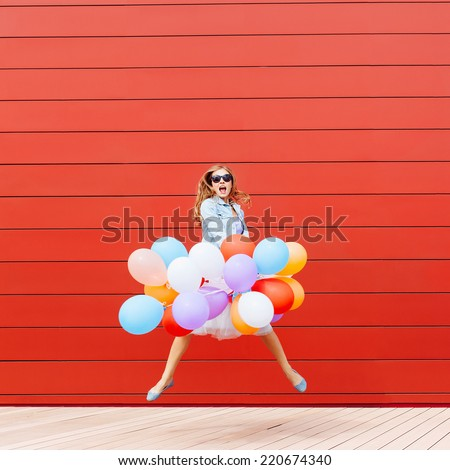 Jumping girl with colorful balloons in her hand. Outside. Red background. Outside - stock photo