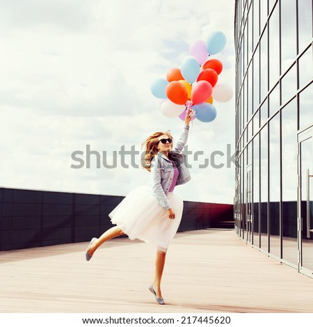 Jumping girl with colorful balloons in one hand. Warm sunny day. Outside. - stock photo