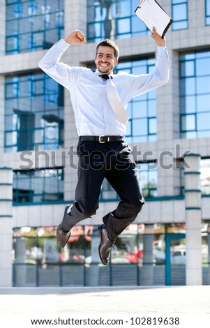 Jumping happy businessman over office buildings - stock photo