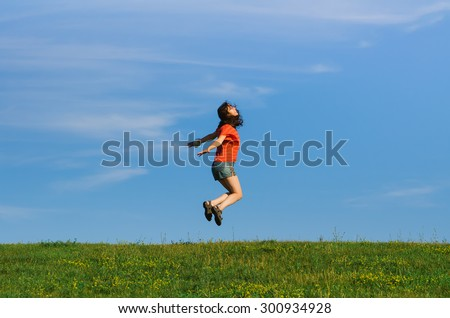 jumping happy emotion woman on grass and sky backgrounds - stock photo