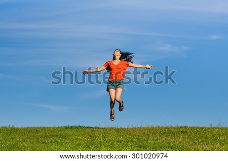 jumping happy emotion woman on grass and sky backgrounds. focus on woman - stock photo