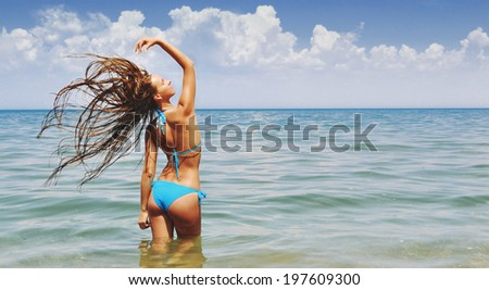 Jumping happy girl on the beach, fit sporty healthy sexy body in bikini, woman enjoys wind, freedom, vacation, summertime fun concept - stock photo