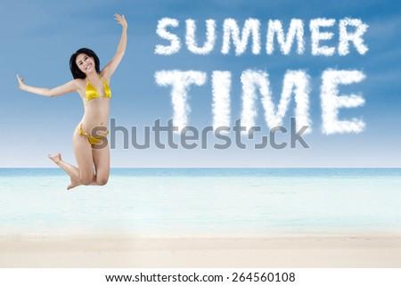 Jumping happy girl wearing bikini on the beach - stock photo
