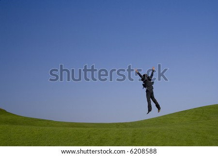 jumping high on a beautiful green and blue landscape - stock photo