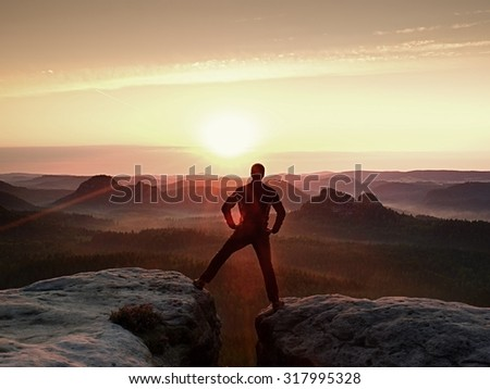 Jumping hiker in black celebrate triumph between two rocky peaks. Wonderful daybreak.